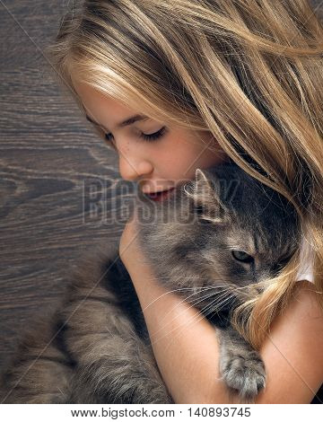 Young beautiful girl with long blond hair tenderly hugging gray fluffy cat