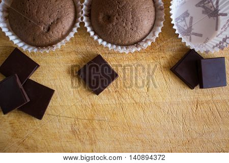 cup cake stand on the Board,on the Desk near a lot of chocolate cupcakes on the table scattered chocolate. Brilliant chocolate cream. Empty basket then pour in raw dough and then they are already ready. chocolate