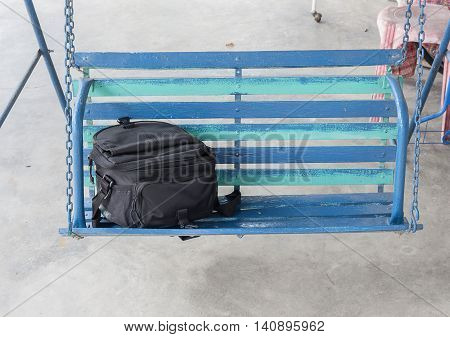 Bag Black on Porch swings Beautiful black camera bag Located on wooden front porch swing : select focus Bag Black :