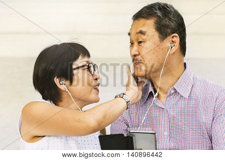 Asian Senior Couple Earphones Concept