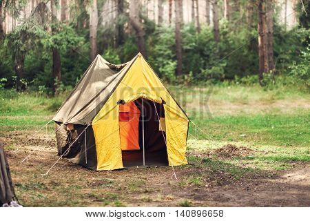 Tourist tent stands in the middle of the forest.