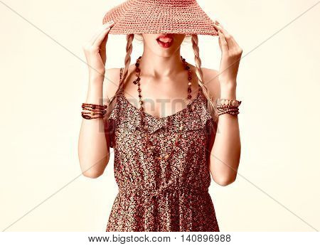 Hippie Boho woman Having Fun. Playful Model licking lips, Summer Fashion Outfit. Blonde in Trendy Sundress, pigtails, Fashion Accessories. Hat covers girl face, romantic fashion Style. Unusual creative