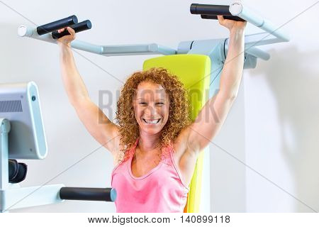 Motivated athletic female in red curly hair and pink top with arms in the raised position with shoulder strengthening machine