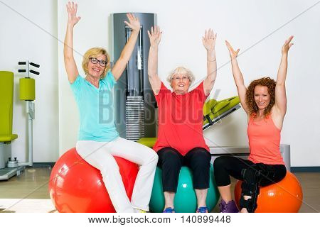 Pair of happy patients with physical therapist stretching arm and shoulder muscles while seated on stability balance balls
