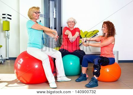 Pair Of Patients With Instructor Stretching Wrists