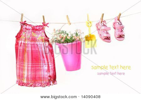 Little girl clothes and toys on a clothesline against white background