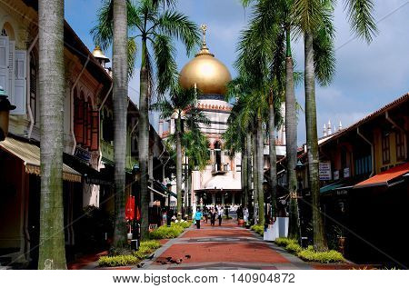 Singpore - December 17 2007: Bussorah Street lined with shops and royal palm trees leading to the 1924-28 Masjid Sultan Singapura Mosque in the historic Kampong Glam Arab district