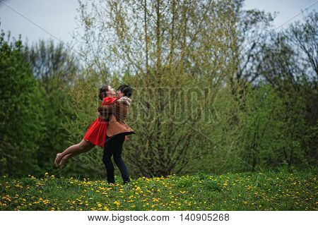 Couple Hugging In Love Background Yellow Flowers Field. Stylish Man At Velvet Jacket Hold Inf Hands
