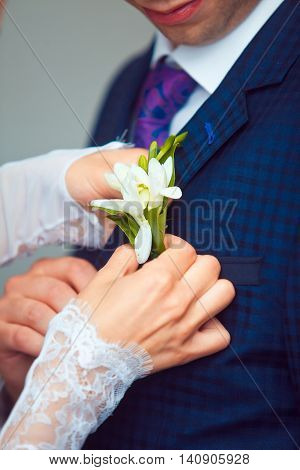 hang of a bride adjusting boutonniere on grooms jacket.