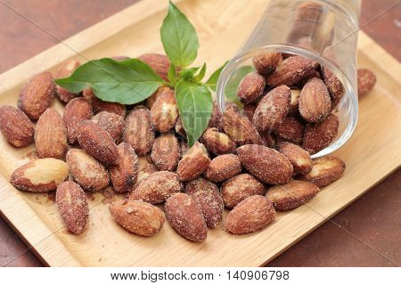 Almonds nuts with salt on wood background