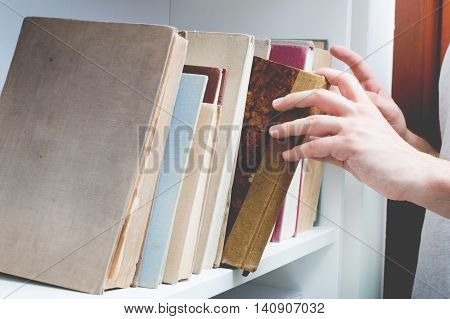 Man chose book from bookshelf. Image performed in vintage stylization.