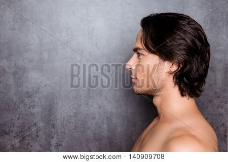 Portrait Of Side-view Of Young Man With Black Hair Near Gray Wall