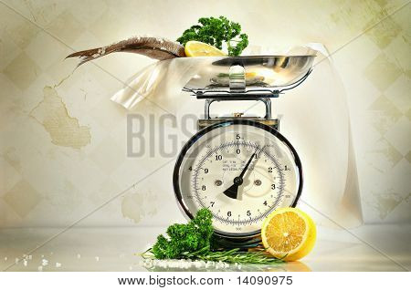 Weight scale with fish and lemons against a grungy, antique background