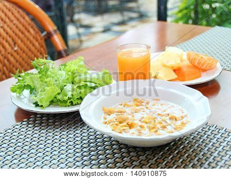 Breakfast with cornflakes, juce, vegetables and fruits