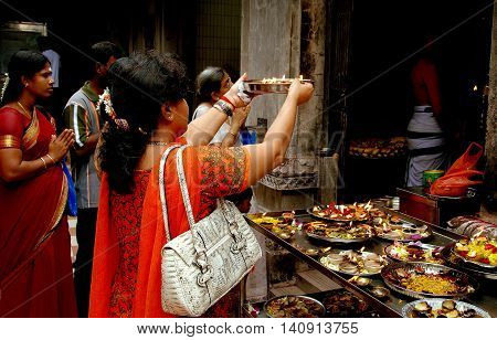 Singapore - December 16 2007: Woman makes an offering wth a silver bowl containing food and lighted candles at the Sri Veeramakaliamman Hindu Temple in Little India