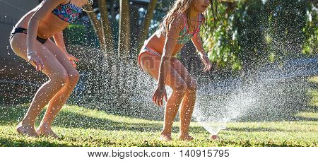 Young Girls Playing Jumping In A Garden Water Lawn Sprinkler