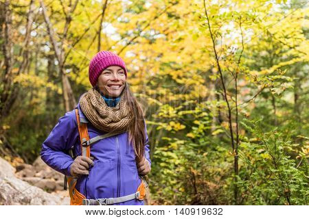 Happy Asian woman hiking in autumn forest nature walking on trail path. Hiker girl with backpack, hat, scarf and jacket on fall adventure travel outdoors good weather during hike in cold weather.