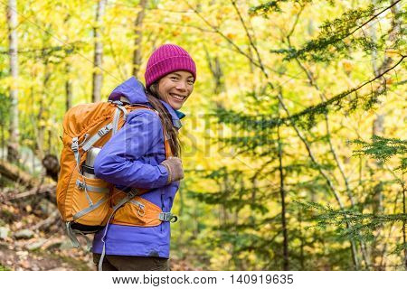 Happy backpacker girl hiking in autumn forest. Young Asian hiker woman in outdoor gear for cold weather with backpack looking at camera enjoying walking in nature outdoors in fall season.