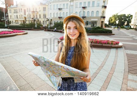 stylish traveler hipster woman portrait with camera and hat holding map on the street travel or exploring concept