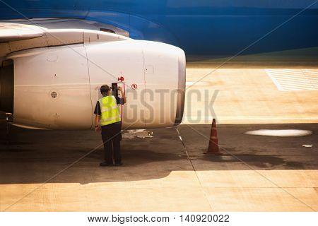 Aircraft mechanic checking airplane jet engine, transportation & logistic