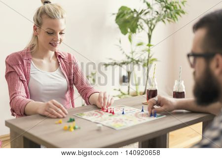 Couple in love sitting on the floor next to a table playing ludo board game and enjoying their free time together. Woman repositioning her figurines and winning the game