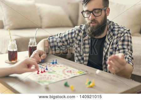 Couple in love sitting on the floor next to a table playing ludo board game and enjoying their free time together. Man throwing dices for his next move
