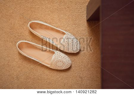 Pair of new unlaced womans shoes on a white wooden floor.