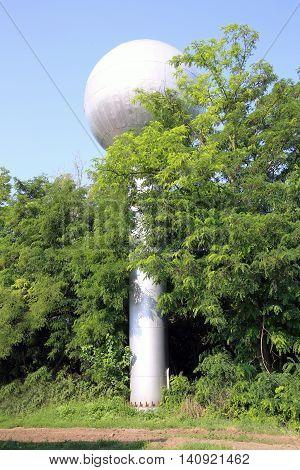 View of globular water tower at village farm between trees