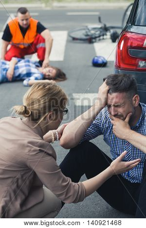 Crying man sitting on the street with the rescue action behind him