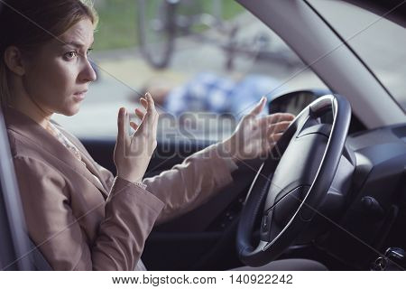 Frightened woman sitting behind the wheel in place of a crash