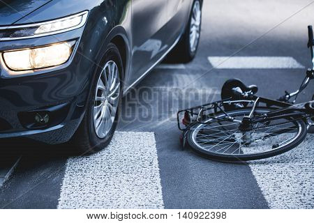 Car standing on the pedestrian path with the downed bicycle