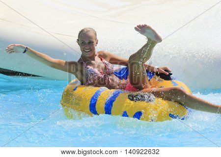 Rhodes Greece-July 30 2016:The girl joying after rafting slide in the Water park.Rafting slide is one of many popular game for adults and children in park. Water Park is located  on the island of Rhodes in Greece and one of the most largest