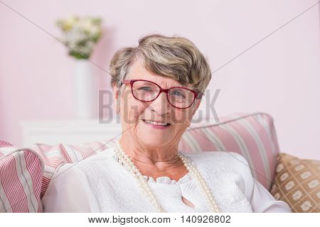 Portrait od smiled senior woman sitting on a couch with pillows
