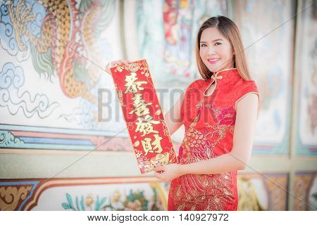 The Asian Woman In Chinese Dress Holding Couplet 'strong.' (chinese Blessing Word) With Chinese Temp