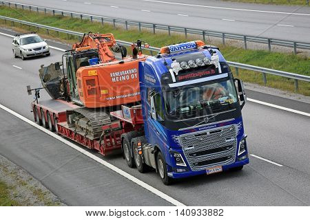 SALO, FINLAND - JULY 31, 2016: Volvo FH16 600 hauls Hitachi tracked excavator on Noteboom trailer along freeway in South of Finland.