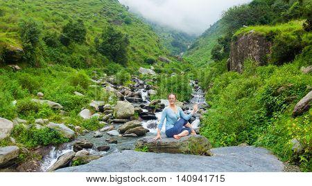 Yoga exercise outdoors -  panorama of woman doing Ardha matsyendrasanaasana asana - half spinal twist pose at tropical waterfall in Himalayas in India. Panoramic image