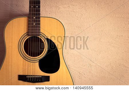 acoustic guitar on beige background vintage wall.