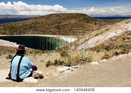 South America Bolivia - Isla del Sol on the Titicaca lake the largest highaltitude lake in the world. Woman siting in the traditional dress on the lake Titicaca