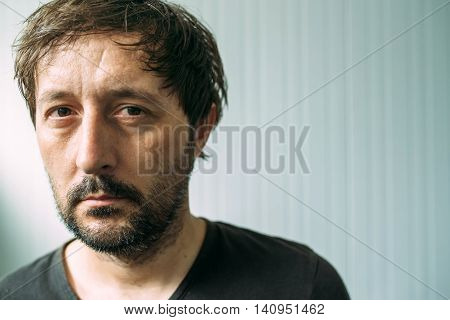 Portrait od miserable and tired adult man depressive male with serious face expression
