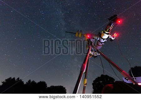 Astrophotography setup in clear night. Refractor type telescope. Telescope in real starry night. Blurred night. Red astronomy lights