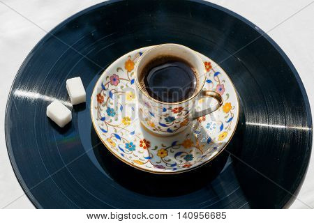 Morning relaxation with old style music concept. Record vinyl and cup of coffee with sugar on it.