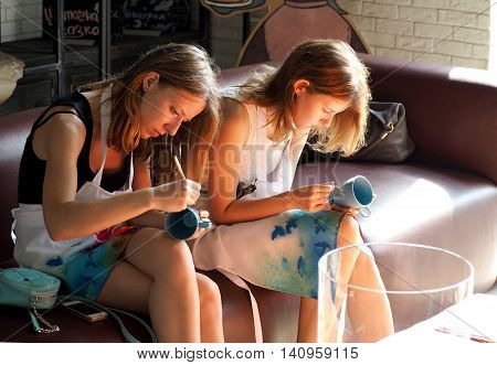 MOSCOW, RUSSIA - July 30, 2016: Two late teens girls painting on mugs. Free activities for adults and children in Moscow. July 30, 2016 in Moscow, Russia
