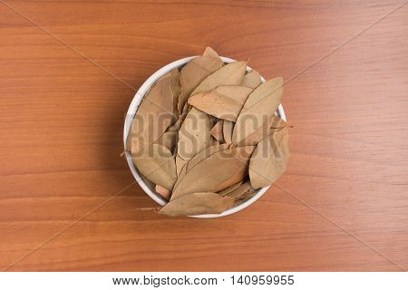 Bulk Bay Leaves into a bowl over a wooden table. (Laurus nobilis)