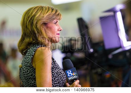 Mechanicsburg PA - August 1 2016: Barbara Barr a reporter for WGAL TV Channel 8 prepares to file a live report.