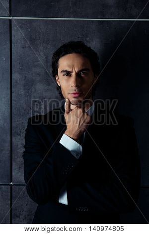 Portrait Of Harsh Young Man In Formalwear Thinking And Holding His Chin
