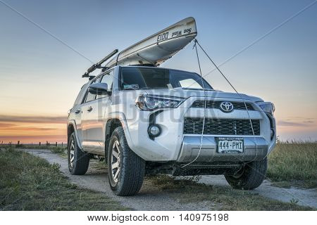 CASTLE ROCK, KS , USA - JULY 25 2016: Toyota 4Runner SUV (2016 Trail edition) with a canoe (Sea Wind by Kruger Canoes) on roof racks driving during summer vacations on Kansas  back country roads