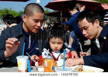 Hong Kong China - January 2 2008: Little Chinese boy with his father and uncle having lunch on the outdoor terrace at Ocean Park's Light House Grill