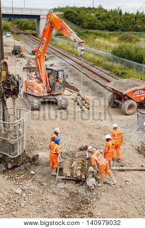 ILKESTON ENGLAND - AUGUST 1: Construction workers moving helical pile drill screws on site next to a section of railway track. In Ilkeston Derbyshire England. On 1st August 2016.