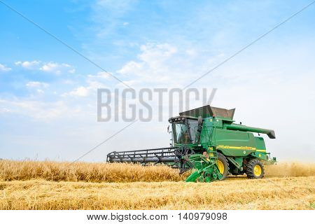 ZAPORIZHZHYA, UKRAINE - July 28, 2015: John Deere Combine Harvester Harvesting Wheat in the Field.