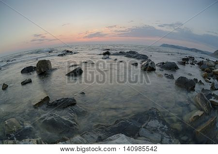 Sunset over the coast with stones of Black Sea, Russia. Fish-eye lens.